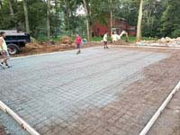Preparing form to receive concrete for base for graphite and orange residential basketball court replacing a dead pool in Walpole, MA.