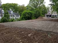 Area cleared and gravel/sand packed to build foundation for black and grey home backyard basketball court in Wellesley, MA.
