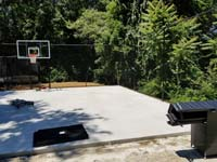 Dry concrete base is ready for installation of low impact tiles for black and grey home backyard basketball court in Wellesley, MA.
