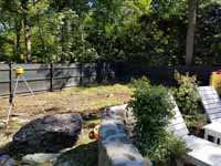 View of the yard where the court will go, before starting in earnest the Chestnut Hill, MA transformation of a tight backyard space into a slate green basketball court with custom containment net fencing atop wooden fence.