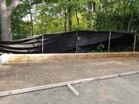 This shows the back of the form, unusually deep, and the metal reinforcement in place prior to poring the back half of the court base for the Chestnut Hill, MA transformation of a tight backyard space into a slate green basketball court with custom containment net fencing atop wooden fence.