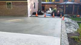 This shows the still damp cement from the pour of the front half of the base, and part of the already cured concrete poured and allowed to dry in the deeper back part for the Chestnut Hill, MA transformation of a tight backyard space into a slate green basketball court with custom containment net fencing atop wooden fence.