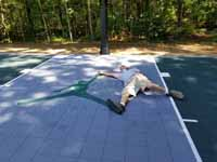 Slate green and titanium backyard basketball court with Michael Jordan custom logo in Duxbury, MA, showing homeowner having fun posing with celebrity likeness.