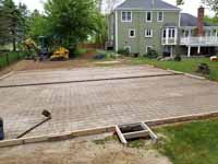 Site work preparing for olive green and yellow basketball court in Easton, MA, featuring lighting extension on goal system for night play. Ground has been prepared and this shows the form and rebar awaiting cement pour to create a quality base.
