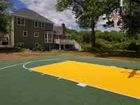 Olive green and yellow basketball court in Easton, MA, featuring lighting extension on goal system for night play.