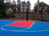 Bright blue and red backyard basketball court nearing completion in Halifax, MA.