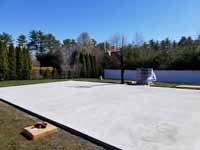 Concrete court base before installing tiles for Titanium and navy blue residential basketball court in Hanson, MA. Form for pouring cement for court base shown here.