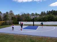 People enjoying new Titanium and navy blue residential basketball court in Hanson, MA.