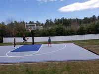 People playing on newly installed Titanium and navy blue residential basketball court in Hanson, MA. Recently poured base shown here, waiting for cement to dry and cure.