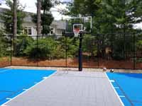 Residential backyard basketball court on asphalt in Massachusetts, in colorful blue and silver.
