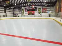 We traveled to Kapolei, Hawaii and inside to resurface two inline skate hockey rinks with Versacourt Speed Indoor tile. This is a look toward one end of the rink, from center line, showing it almost complete except edge tiles.