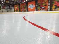 We traveled to Kapolei, Hawaii and inside to resurface two inline skate hockey rinks with Versacourt Speed Indoor tile. This is a finished view showing part of the faceoff circle and the adjacent skating surface.