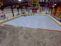 We traveled to Kapolei, Hawaii and inside to resurface two inline skate hockey rinks with Versacourt Speed Indoor tile. This is a long, high view of much of the length of the first court in mid-install.