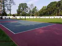 Red and slate green tennis and basketball multicourt on concrete base in Lakeville, MA.