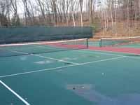 Decrepit tennis court in Manchester, NH repurposed and freshly surfaced as a basketball court in blue and red. Complete except paint over the exposed old surfaces around the new court. Part of the old tennis court shown here.