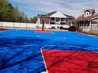 Decrepit tennis court in Manchester, NH repurposed and freshly surfaced as a basketball court in blue and red. Complete except paint over the exposed old surfaces around the new court.