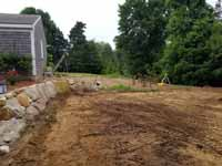 Charcoal and titanium Cape Cod backyard basketball court in Barnstable village of Marstons Mills, MA. Before picture with the ground being prepared to allow a base to be installed. Compare to after picture to right.