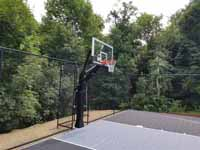 Charcoal and titanium Cape Cod backyard basketball court in Barnstable village of Marstons Mills, MA. Close-up view of hoop system.