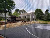 Charcoal and titanium Cape Cod backyard basketball court in Barnstable village of Marstons Mills, MA. Looking through fencing, an option this homeowner selected.