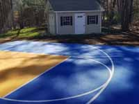Home basketball court in Medway, MA, featuring royal blue and yellow Versacourt outdoor sport surface tiles.