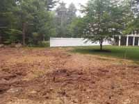 Backyard basketball court with graphite and red Versacourt surface in Middleborough, MA. Site shown here after trees had been removed and ground prepared, but before base and court installation.