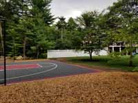 Backyard basketball court with graphite and red Versacourt surface in Middleborough, MA.