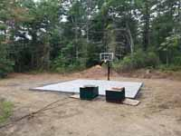 Green and red residential basketball court in Middleborough, MA. Shown here: Completed concrete base and installed goal system, with pallets of court tiles awaiting installation.