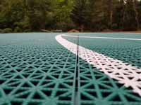 Green and red residential basketball court in Middleborough, MA. Closeup of white line also shows tile detail, designed for comfort and drainage.