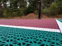 Green and red residential basketball court in Middleborough, MA. This is detail of the tile surface, designed to drain water so there's no puddling.
