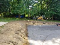 Back left end of excavated and leveled site with stone dust underlay in prep for monochrome blue hilltop home basketball court in Milton, MA.