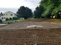 Form and reinforcement about ready for cement to cure into concrete base for monochrome blue hilltop home basketball court in Milton, MA.