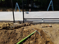 Runoff management work in progress for monochrome blue hilltop home basketball court in Milton, MA.