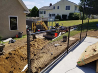 Runoff control work in progress for monochrome blue hilltop home basketball court in Milton, MA.