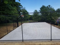 All the leveling and preparation is done, concrete base is in, and fence is up for monochrome blue hilltop home basketball court in Milton, MA.