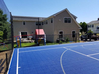 Monochrome blue hilltop home basketball court in Milton, MA.