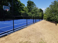 Monochrome blue hilltop home basketball court in Milton, MA. Runoff collector is visible alongside court.