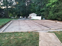 Light blue, red, and royal blue residential basketball court in North Attleboro, MA. Form for pouring cement for court base shown here.