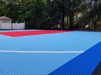 Light blue, red, and royal blue residential basketball court in North Attleboro, MA.