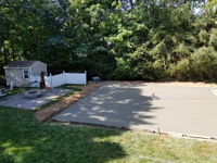 Light blue, red, and royal blue residential basketball court in North Attleboro, MA. Recently poured base shown here, waiting for cement to dry and cure.