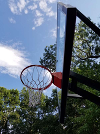 Light blue, red, and royal blue residential basketball court in North Attleboro, MA, showing closeup of hoop from below.