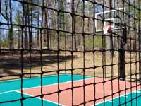 Residential basketball court in Norwell, MA, including goal system, mesh fencing, and an emerald green and rust red tile sport surface. Some trees and stumps were removed to make room in the yard and provide easy work access. This is a view of part of the court through the mesh fence.