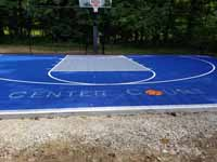 The words CENTER COURT on a small backyard basketball court, with the O in court replaced by an orange basketball.