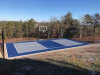 Multicourt for pickleball and basketball, fenced on three sides, on a hillside backyard in Plymouth, MA. View after construction completed.