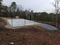 Hillside court primarily for pickleball, accessorized with a basketball goal and fencing, in Plymouth, MA. Side view looks good considering court surface tiles remain to be installed.