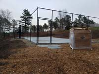 Multicourt for pickleball and basketball, fenced on three sides, on a hillside backyard in Plymouth, MA. Fenced court base from the gate end, with pallet of Versacourt tiles in foreground, waiting to be installed to finish the process.
