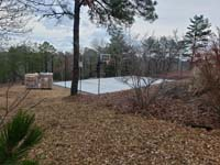 Hillside court primarily for pickleball, accessorized with a basketball goal and fencing, in Plymouth, MA. View from adjancent yard above after base and fence installation.