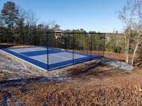 Multicourt for pickleball and basketball, fenced on three sides, on a hillside backyard in Plymouth, MA. Finished blue and grey court with scenic view beyond.