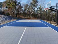 Hillside court primarily for pickleball, accessorized with a basketball goal and fencing, in Plymouth, MA. Finished view from the side.