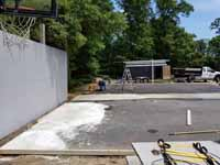Home basketball court upgrade of old asphalt court in Cape Cod village of Pocasset in Bourne, MA. Shown here in process of filling, leveling, and trimming edges to match new court size smoothly.
