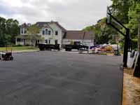 Home basketball court upgrade of old asphalt court in Cape Cod village of Pocasset in Bourne, MA. Shown here after installation of new goal system and uniform surfacing of patched asphalt.